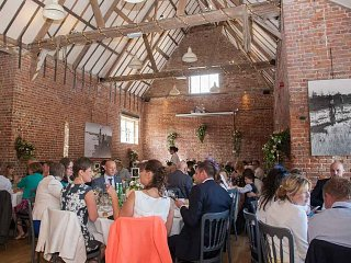 Guests seated for a barn wedding breakfast showing the vaulted roof.